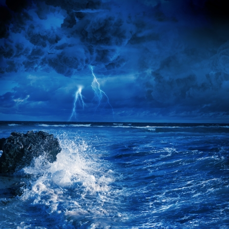 Image of night stormy sea with big waves and lightning photo
