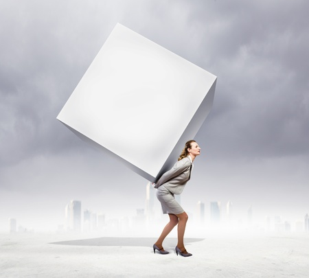 Image of businesswoman carrying big white cube on her back  Place for text photo