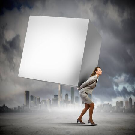 Image of businesswoman carrying big white cube on her back  Place for text