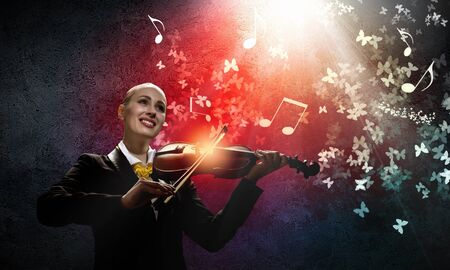 virtuoso: Image of young smiling businesswoman playing violin