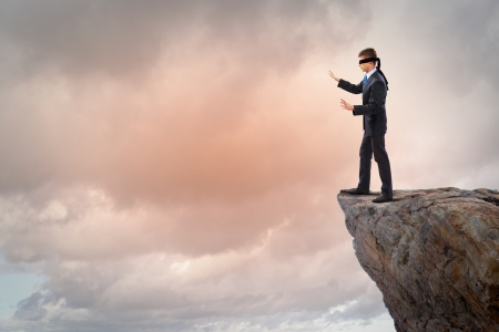 unskilled: Image of businessman in blindfold standing on edge of mountain Stock Photo