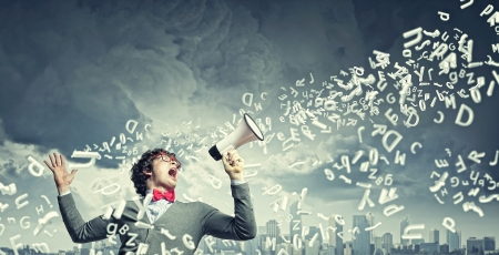 excited: Portrait of young man shouting loudly using megaphone Stock Photo