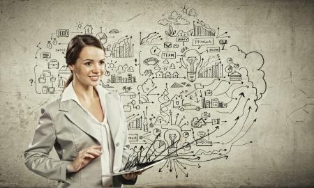 plan van aanpak: Afbeelding van jonge onderneemster die een tablet pc tegen schets achtergrond Stockfoto
