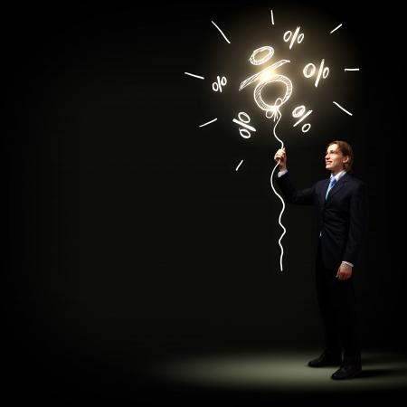 暗い背景に対して黒のスーツのビジネスマンのイメージ 写真素材