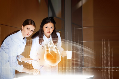 pulmology: Image of two attractive women cardiologist examining virtual heart