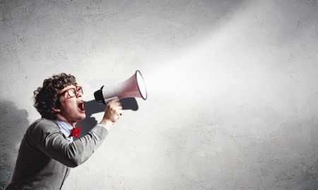 loud speaker: Portrait of young man shouting loudly using megaphone Stock Photo