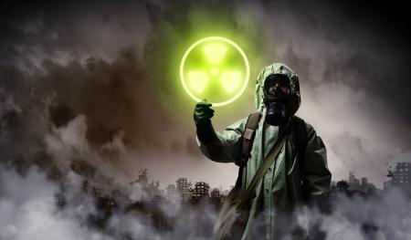 radiactividad: Imagen del hombre en la m�scara de gas y uniforme de protecci�n de tocar signo radiactividad
