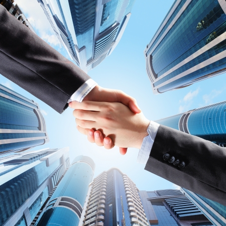 Close up image of hand shake against skyscrapers Stok Fotoğraf