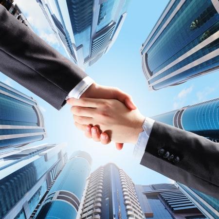 stretta di mano: Close up immagine della stretta di mano contro i grattacieli