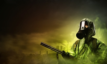 Man in gas mask and camouflage holding gun  Disaster concept