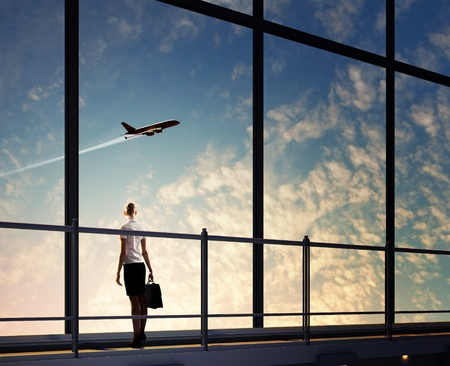 Image of businesswoman at airport looking at airplane taking off photo