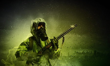 Man in gas mask and camouflage holding gun  Disaster concept photo