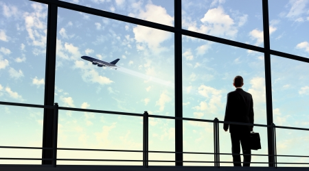 the window: Image of businessman at airport looking at airplane taking off