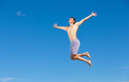 Portrait of a happy young man having fun on the beach on a summer vacation  photo