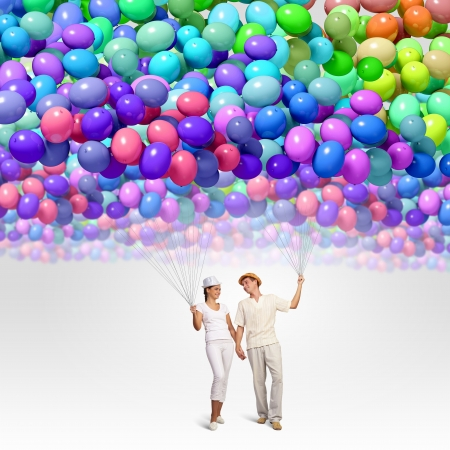 Image of young couple holding bunch of colorful balloons Stock Photo - 21334162