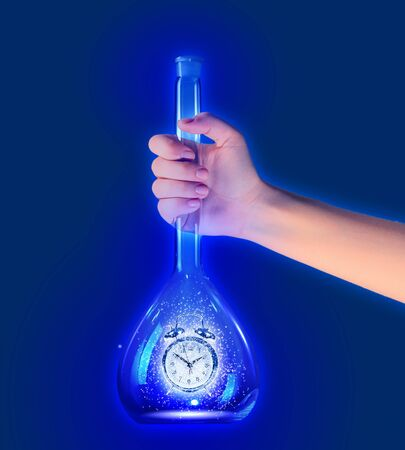 Human hand holding test tube with alarm clock inside photo