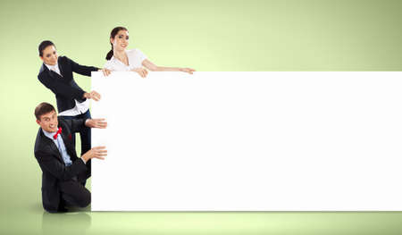 Image of three young people holding blank banner against green background  Place for text photo