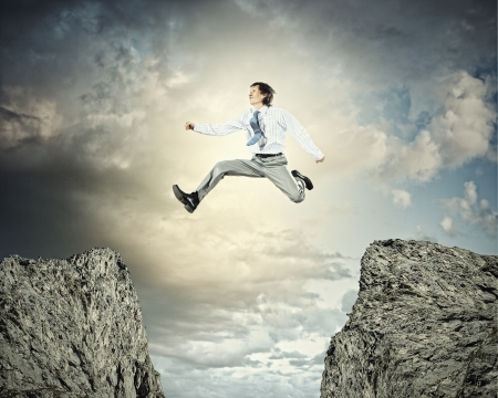 Image of young businessman jumping over gap Stock Photo - 21358531