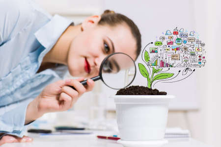 Young businesswoman looking at drawn image of sprout through magnifier photo