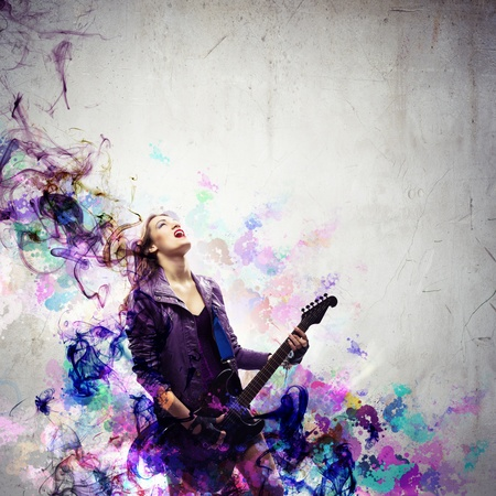 Young attractive rock girl playing the electric guitar photo