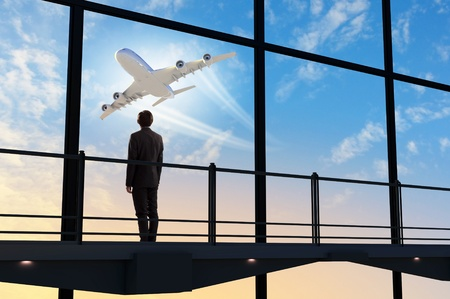 landing: Image of businessman at airport looking at airplane taking off