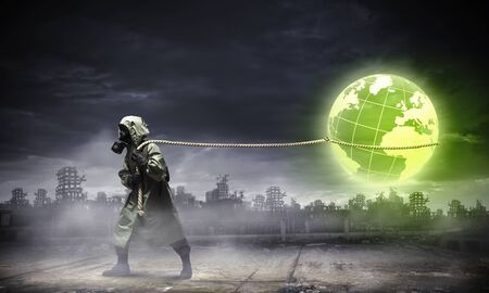 Man in respirator against nuclear background  Global pollution photo