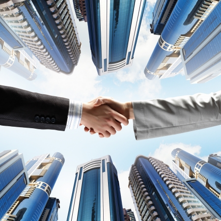 close up image: Close up image of hand shake against skyscrapers Stock Photo