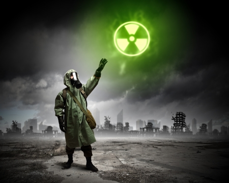 Image of man in gas mask and protective uniform touching radioactivity sign photo