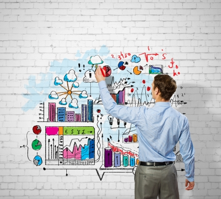 Back view image of businessman drawing sketches on wall Фото со стока