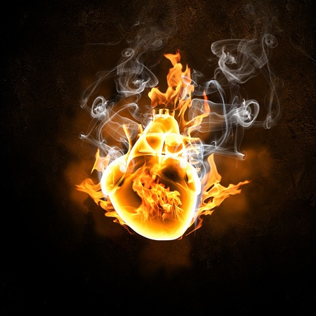 heart burn: Illustration of human heart in fire flames against black background