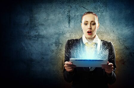 Image of astonished business woman holding tablet photo
