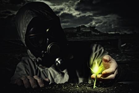 nuke plant: Hombre joven en un traje de protecci?n toca al futuro post-nuclear brotar