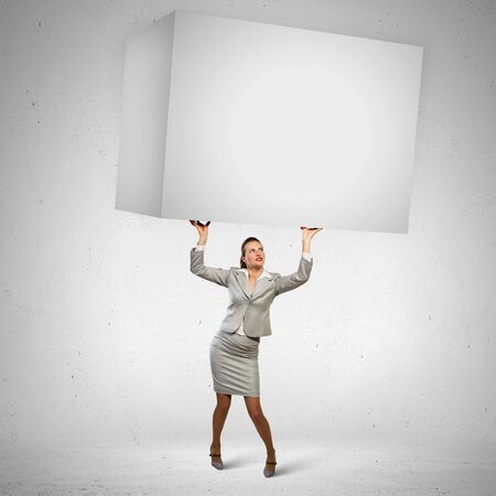 overburdened: Image of business woman holding heavy white cube above head