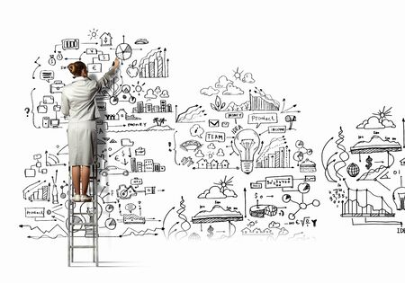 project manager: Back view of businesswoman drawing sketch on wall Stock Photo
