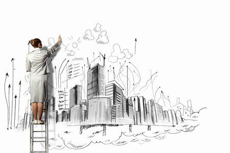 実業家の梯子の上に立って、壁上にスケッチを描画 写真素材