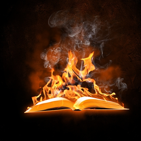 Image of opened burning book against black background photo