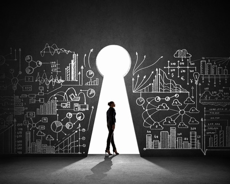 Silhouette of businesswoman against black wall with key hole photo