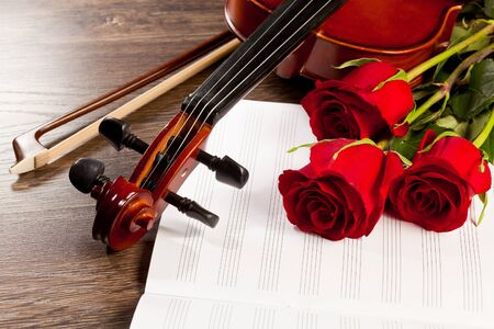 Red roses and a violin on the table photo