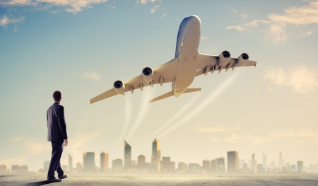 Image of businessman standing with back looking at airplane in sky photo