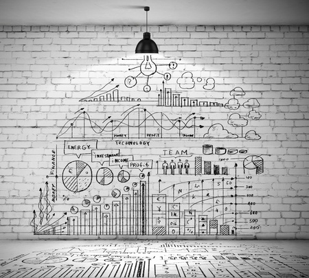 Drawn business plan on wall illuminated by lamp above photo
