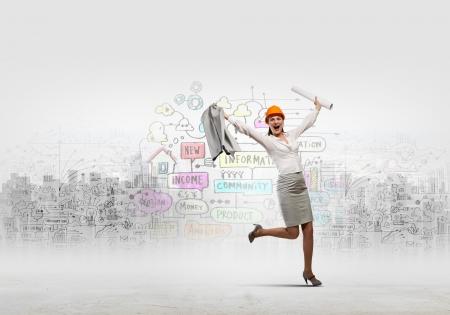 joyfully: Young woman engineer in helmet jumping joyfully