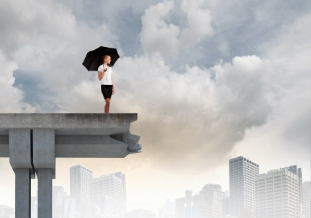 Young businesswoman with umbrella standing on bridge photo