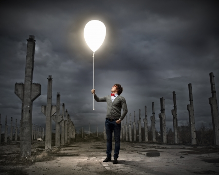 Young man holding a light at his hands against polluted and ruined landscape photo