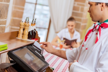 inserting: Image of handsome chef inserting card in terminal Stock Photo