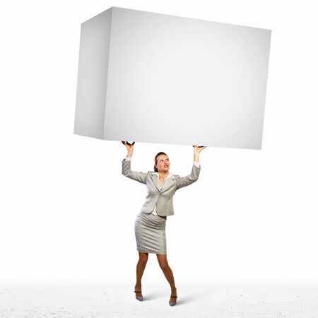 Image of business woman holding heavy white cube above head photo