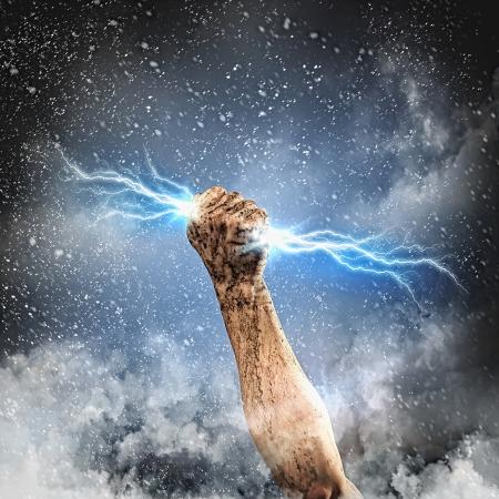 Close-up of human hand clenching lightning flash