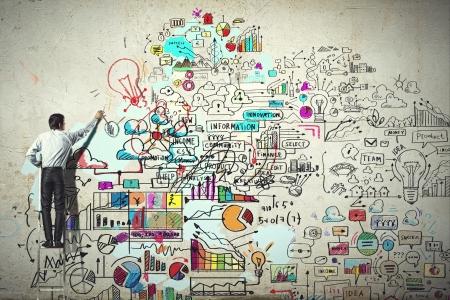 壁上にスケッチを描画の実業家の背面図