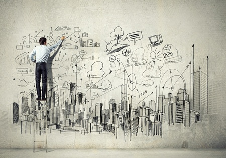 Back view of businessman drawing sketch on wall Stock Photo - 21498658