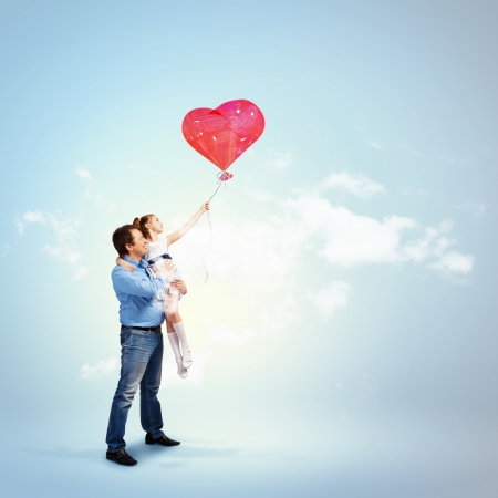 Image of happy father holding his daughter and a red heart baloon photo