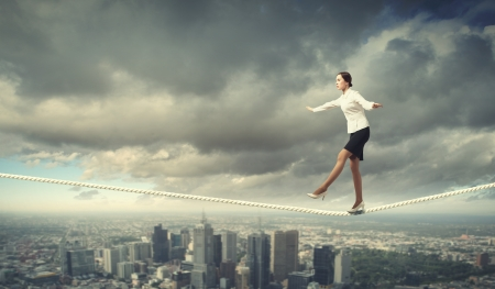 Image of businesswoman balancing on rope  Risk concept Stock Photo